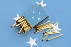 Η σημαία της Μικρονησίας παρουσιάζεται σε ένα ανοικτό σπιρτόκουτο, από το οποίο διάφορες αντιστοιχίες αφορούν και βρίσκονται μια  στοκ εικόνες με δικαίωμα ελεύθερης χρήσης