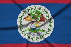 Η σημαία της Μπελίζ απεικονίζεται σε ένα ύφασμα αθλητικών υφασμάτων με πολλές πτυχές Έμβλημα αθλητικών ομάδων στοκ εικόνες
