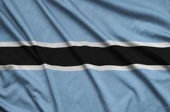 Η σημαία της Μποτσουάνα απεικονίζεται σε ένα ύφασμα αθλητικών υφασμάτων με πολλές πτυχές Έμβλημα αθλητικών ομάδων στοκ εικόνες
