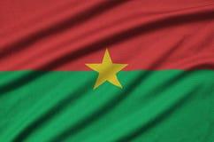 Η σημαία της Μπουρκίνα Φάσο απεικονίζεται σε ένα ύφασμα αθλητικών υφασμάτων με πολλές πτυχές Έμβλημα αθλητικών ομάδων στοκ φωτογραφία με δικαίωμα ελεύθερης χρήσης