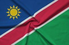 Η σημαία της Ναμίμπια απεικονίζεται σε ένα ύφασμα αθλητικών υφασμάτων με πολλές πτυχές Έμβλημα αθλητικών ομάδων στοκ φωτογραφίες με δικαίωμα ελεύθερης χρήσης
