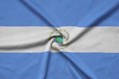 Η σημαία της Νικαράγουας απεικονίζεται σε ένα ύφασμα αθλητικών υφασμάτων με πολλές πτυχές Έμβλημα αθλητικών ομάδων στοκ εικόνες με δικαίωμα ελεύθερης χρήσης