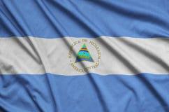 Η σημαία της Νικαράγουας απεικονίζεται σε ένα ύφασμα αθλητικών υφασμάτων με πολλές πτυχές Έμβλημα αθλητικών ομάδων στοκ εικόνες