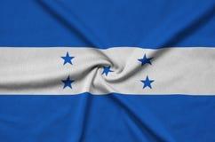 Η σημαία της Ονδούρας απεικονίζεται σε ένα ύφασμα αθλητικών υφασμάτων με πολλές πτυχές Έμβλημα αθλητικών ομάδων στοκ φωτογραφίες με δικαίωμα ελεύθερης χρήσης