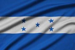 Η σημαία της Ονδούρας απεικονίζεται σε ένα ύφασμα αθλητικών υφασμάτων με πολλές πτυχές Έμβλημα αθλητικών ομάδων στοκ εικόνες