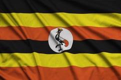 Η σημαία της Ουγκάντας απεικονίζεται σε ένα ύφασμα αθλητικών υφασμάτων με πολλές πτυχές Έμβλημα αθλητικών ομάδων στοκ εικόνες με δικαίωμα ελεύθερης χρήσης