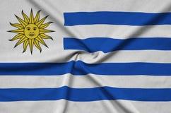 Η σημαία της Ουρουγουάης απεικονίζεται σε ένα ύφασμα αθλητικών υφασμάτων με πολλές πτυχές Έμβλημα αθλητικών ομάδων στοκ φωτογραφία με δικαίωμα ελεύθερης χρήσης