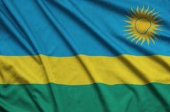 Η σημαία της Ρουάντα απεικονίζεται σε ένα ύφασμα αθλητικών υφασμάτων με πολλές πτυχές Έμβλημα αθλητικών ομάδων στοκ εικόνα με δικαίωμα ελεύθερης χρήσης