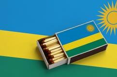 Η σημαία της Ρουάντα παρουσιάζεται σε ένα ανοικτό σπιρτόκουτο, το οποίο γεμίζουν με τις αντιστοιχίες και βρίσκεται σε μια μεγάλη  στοκ φωτογραφία