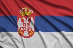 Η σημαία της Σερβίας απεικονίζεται σε ένα ύφασμα αθλητικών υφασμάτων με πολλές πτυχές Έμβλημα αθλητικών ομάδων στοκ εικόνες με δικαίωμα ελεύθερης χρήσης