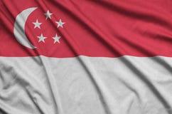 Η σημαία της Σιγκαπούρης απεικονίζεται σε ένα ύφασμα αθλητικών υφασμάτων με πολλές πτυχές Έμβλημα αθλητικών ομάδων στοκ εικόνες με δικαίωμα ελεύθερης χρήσης