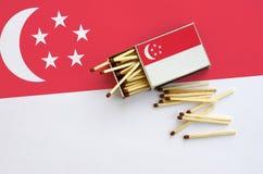 Η σημαία της Σιγκαπούρης παρουσιάζεται σε ένα ανοικτό σπιρτόκουτο, από το οποίο διάφορες αντιστοιχίες αφορούν και βρίσκονται μια  στοκ εικόνες