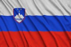 Η σημαία της Σλοβενίας απεικονίζεται σε ένα ύφασμα αθλητικών υφασμάτων με πολλές πτυχές Έμβλημα αθλητικών ομάδων στοκ εικόνα