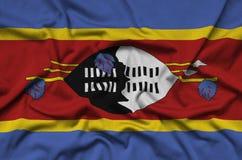 Η σημαία της Σουαζιλάνδης απεικονίζεται σε ένα ύφασμα αθλητικών υφασμάτων με πολλές πτυχές Έμβλημα αθλητικών ομάδων στοκ φωτογραφία με δικαίωμα ελεύθερης χρήσης