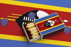 Η σημαία της Σουαζιλάνδης παρουσιάζεται σε ένα ανοικτό σπιρτόκουτο, το οποίο γεμίζουν με τις αντιστοιχίες και βρίσκεται σε μια με στοκ φωτογραφία με δικαίωμα ελεύθερης χρήσης