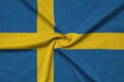 Η σημαία της Σουηδίας απεικονίζεται σε ένα ύφασμα αθλητικών υφασμάτων με πολλές πτυχές Έμβλημα αθλητικών ομάδων στοκ εικόνα με δικαίωμα ελεύθερης χρήσης