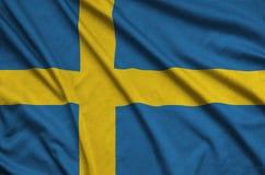 Η σημαία της Σουηδίας απεικονίζεται σε ένα ύφασμα αθλητικών υφασμάτων με πολλές πτυχές Έμβλημα αθλητικών ομάδων στοκ φωτογραφία