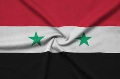 Η σημαία της Συρίας απεικονίζεται σε ένα ύφασμα αθλητικών υφασμάτων με πολλές πτυχές Έμβλημα αθλητικών ομάδων στοκ φωτογραφία
