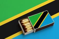 Η σημαία της Τανζανίας παρουσιάζεται σε ένα ανοικτό σπιρτόκουτο, το οποίο γεμίζουν με τις αντιστοιχίες και βρίσκεται σε μια μεγάλ στοκ φωτογραφίες