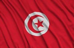 Η σημαία της Τυνησίας απεικονίζεται σε ένα ύφασμα αθλητικών υφασμάτων με πολλές πτυχές Έμβλημα αθλητικών ομάδων στοκ εικόνα