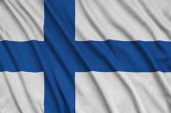 Η σημαία της Φινλανδίας απεικονίζεται σε ένα ύφασμα αθλητικών υφασμάτων με πολλές πτυχές Έμβλημα αθλητικών ομάδων στοκ φωτογραφία με δικαίωμα ελεύθερης χρήσης