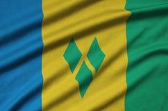 Η σημαία του Άγιου Βικεντίου και Γρεναδίνες απεικονίζεται σε ένα ύφασμα αθλητικών υφασμάτων με πολλές πτυχές Έμβλημα αθλητικών ομ στοκ φωτογραφίες με δικαίωμα ελεύθερης χρήσης