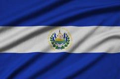 Η σημαία του Ελ Σαλβαδόρ απεικονίζεται σε ένα ύφασμα αθλητικών υφασμάτων με πολλές πτυχές Έμβλημα αθλητικών ομάδων στοκ εικόνες