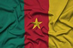 Η σημαία του Καμερούν απεικονίζεται σε ένα ύφασμα αθλητικών υφασμάτων με πολλές πτυχές Έμβλημα αθλητικών ομάδων στοκ εικόνα με δικαίωμα ελεύθερης χρήσης