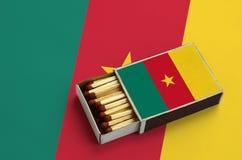 Η σημαία του Καμερούν παρουσιάζεται σε ένα ανοικτό σπιρτόκουτο, το οποίο γεμίζουν με τις αντιστοιχίες και βρίσκεται σε μια μεγάλη στοκ εικόνα με δικαίωμα ελεύθερης χρήσης