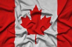 Η σημαία του Καναδά απεικονίζεται σε ένα ύφασμα αθλητικών υφασμάτων με πολλές πτυχές Έμβλημα αθλητικών ομάδων στοκ εικόνα