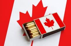 Η σημαία του Καναδά παρουσιάζεται σε ένα ανοικτό σπιρτόκουτο, το οποίο γεμίζουν με τις αντιστοιχίες και βρίσκεται σε μια μεγάλη σ στοκ φωτογραφία
