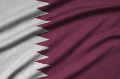 Η σημαία του Κατάρ απεικονίζεται σε ένα ύφασμα αθλητικών υφασμάτων με πολλές πτυχές Έμβλημα αθλητικών ομάδων στοκ εικόνες με δικαίωμα ελεύθερης χρήσης