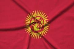 Η σημαία του Κιργιστάν απεικονίζεται σε ένα ύφασμα αθλητικών υφασμάτων με πολλές πτυχές Έμβλημα αθλητικών ομάδων στοκ φωτογραφίες με δικαίωμα ελεύθερης χρήσης