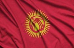 Η σημαία του Κιργιστάν απεικονίζεται σε ένα ύφασμα αθλητικών υφασμάτων με πολλές πτυχές Έμβλημα αθλητικών ομάδων στοκ φωτογραφίες