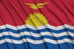 Η σημαία του Κιριμπάτι απεικονίζεται σε ένα ύφασμα αθλητικών υφασμάτων με πολλές πτυχές Έμβλημα αθλητικών ομάδων στοκ εικόνα με δικαίωμα ελεύθερης χρήσης