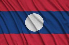 Η σημαία του Λάος απεικονίζεται σε ένα ύφασμα αθλητικών υφασμάτων με πολλές πτυχές Έμβλημα αθλητικών ομάδων στοκ εικόνα με δικαίωμα ελεύθερης χρήσης