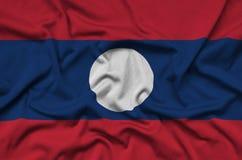 Η σημαία του Λάος απεικονίζεται σε ένα ύφασμα αθλητικών υφασμάτων με πολλές πτυχές Έμβλημα αθλητικών ομάδων στοκ φωτογραφίες με δικαίωμα ελεύθερης χρήσης