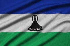Η σημαία του Λεσόθο απεικονίζεται σε ένα ύφασμα αθλητικών υφασμάτων με πολλές πτυχές Έμβλημα αθλητικών ομάδων στοκ εικόνες με δικαίωμα ελεύθερης χρήσης