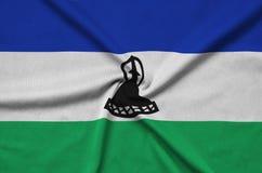 Η σημαία του Λεσόθο απεικονίζεται σε ένα ύφασμα αθλητικών υφασμάτων με πολλές πτυχές Έμβλημα αθλητικών ομάδων στοκ εικόνες