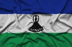 Η σημαία του Λεσόθο απεικονίζεται σε ένα ύφασμα αθλητικών υφασμάτων με πολλές πτυχές Έμβλημα αθλητικών ομάδων στοκ φωτογραφίες με δικαίωμα ελεύθερης χρήσης