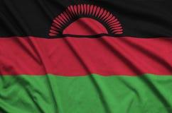 Η σημαία του Μαλάουι απεικονίζεται σε ένα ύφασμα αθλητικών υφασμάτων με πολλές πτυχές Έμβλημα αθλητικών ομάδων στοκ φωτογραφία με δικαίωμα ελεύθερης χρήσης