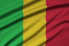 Η σημαία του Μαλί απεικονίζεται σε ένα ύφασμα αθλητικών υφασμάτων με πολλές πτυχές Έμβλημα αθλητικών ομάδων στοκ φωτογραφίες με δικαίωμα ελεύθερης χρήσης