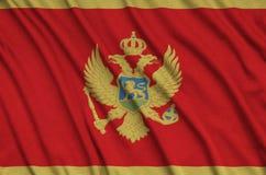Η σημαία του Μαυροβουνίου απεικονίζεται σε ένα ύφασμα αθλητικών υφασμάτων με πολλές πτυχές Έμβλημα αθλητικών ομάδων στοκ εικόνα με δικαίωμα ελεύθερης χρήσης