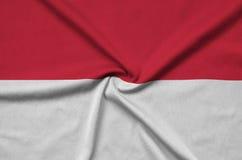 Η σημαία του Μονακό απεικονίζεται σε ένα ύφασμα αθλητικών υφασμάτων με πολλές πτυχές Έμβλημα αθλητικών ομάδων στοκ εικόνες με δικαίωμα ελεύθερης χρήσης