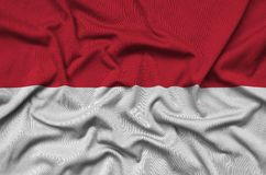 Η σημαία του Μονακό απεικονίζεται σε ένα ύφασμα αθλητικών υφασμάτων με πολλές πτυχές Έμβλημα αθλητικών ομάδων στοκ εικόνα με δικαίωμα ελεύθερης χρήσης
