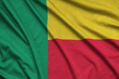 Η σημαία του Μπενίν απεικονίζεται σε ένα ύφασμα αθλητικών υφασμάτων με πολλές πτυχές Έμβλημα αθλητικών ομάδων στοκ φωτογραφία με δικαίωμα ελεύθερης χρήσης