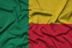 Η σημαία του Μπενίν απεικονίζεται σε ένα ύφασμα αθλητικών υφασμάτων με πολλές πτυχές Έμβλημα αθλητικών ομάδων στοκ εικόνες με δικαίωμα ελεύθερης χρήσης