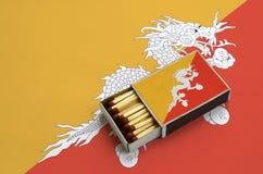 Η σημαία του Μπουτάν παρουσιάζεται σε ένα ανοικτό σπιρτόκουτο, το οποίο γεμίζουν με τις αντιστοιχίες και βρίσκεται σε μια μεγάλη  στοκ φωτογραφία
