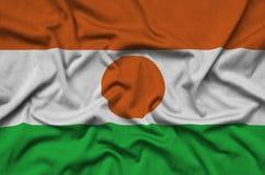 Η σημαία του Νίγηρα απεικονίζεται σε ένα ύφασμα αθλητικών υφασμάτων με πολλές πτυχές Έμβλημα αθλητικών ομάδων στοκ εικόνα με δικαίωμα ελεύθερης χρήσης