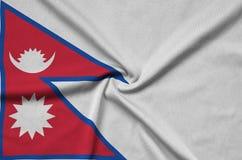 Η σημαία του Νεπάλ απεικονίζεται σε ένα ύφασμα αθλητικών υφασμάτων με πολλές πτυχές Έμβλημα αθλητικών ομάδων στοκ φωτογραφίες
